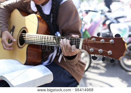 Teenage School Girl Playing An Acoustic Guitar