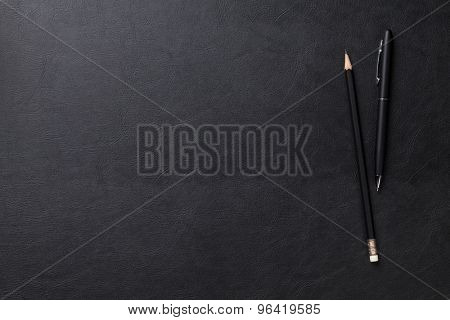 Office leather desk table with pen and pencil. Top view with copy space
