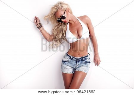 Sexy beautiful blonde woman posing in fashionable sunglasses and swimwear. Studio shot. Girl with perfect tanned body. Girl with long healthy hair. poster