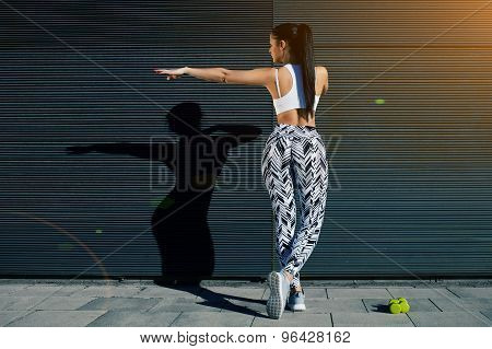 Young woman with perfect figure stretching her hands against black wall with copy space