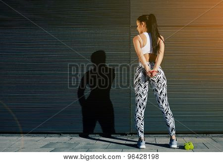 Back view fit female in sportswear squatting after training on black background with copy space