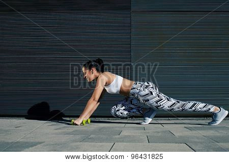 Young fit female in workout gear doing push-ups on black background with copy space outdoors