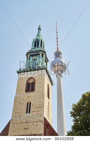 BERLIN, GERMANY - JULY 07: Low angle shot of TV tower in Alexanderplatz, with Saint Mary's Church tower in the foreground. July 07, 2015 in Berlin.