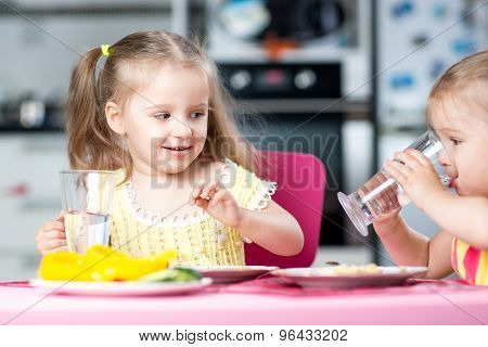 Cute little children drinking water at daycare