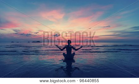 Woman doing meditation near the ocean beach. Yoga silhouette.