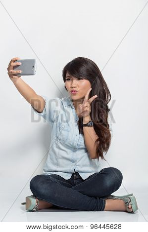 Young Woman Sitting On The Floor Taking Self Camera