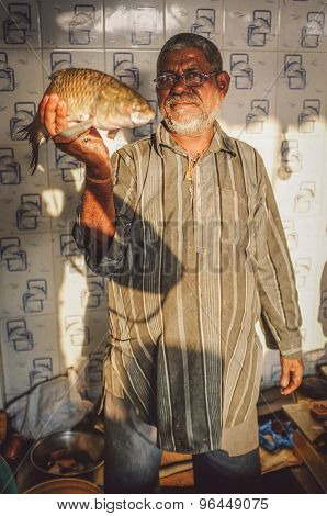 MUMBAI, INDIA - 08 JANUARY 2015: Worker on a fishmarket next to Dhobi ghat showing a fish while waiting for customers. Post-processed with grain, texture and colour effect.