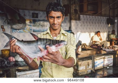 MUMBAI, INDIA - 08 JANUARY 2015: Worker on a fishmarket next to Dhobi ghat shows fish while waiting for customers. Post-processed with grain, texture and colour effect.