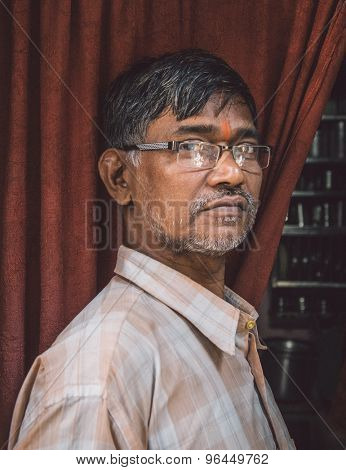MUMBAI, INDIA - 12 JANUARY 2015: Elderly Indian man with glasses and bindi stands in doorway of home. Post-processed with grain, texture and colour effect.