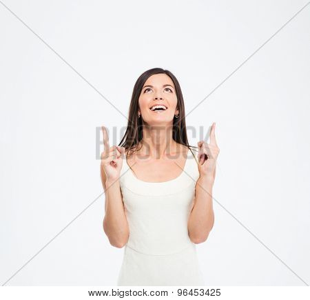 Cheerful woman pointing finger up at copyspace isolated on a white background