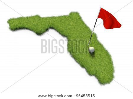 Golf ball and flag pole on course putting green shaped like the state of Florida