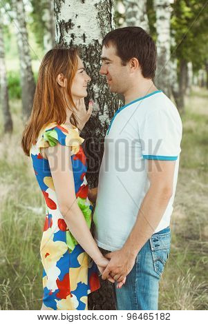 Young couple holding hands in the park among birches. poster