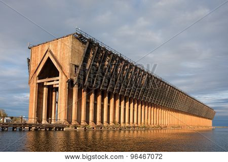 Abandoned ore dock once used to transfer coal and other materials between railroad cars and Lake Superior ore boats. Interesting geometric structure captured near sunset. Warm light and a dramatic sky. poster