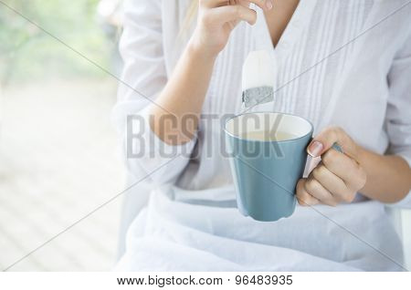 Closeup shot of a woman dipping tea bag into cup with hot water. Young woman drinking tea. Close up of girl's hand dipping tea bag into mug. Shallow depth of field with focus on dipping teabag.