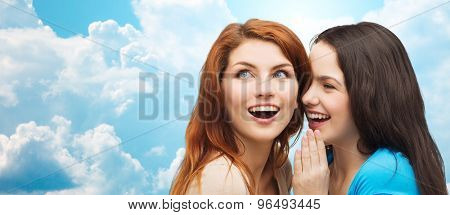 friendship, secrecy and people concept - two smiling girls or young women whispering gossip over blue sky with clouds background