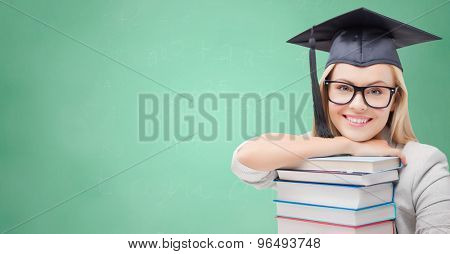 education, high school, knowledge, and people concept - picture of happy student girl or woman in trencher cap with stack of books over green chalk board background