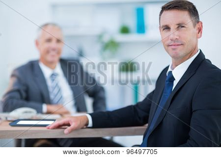 Confident businessman looking at camera with colleague behind in the office