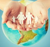 people, population, charity and life concept - close up of human hands holding paper family over earth globe and blue background poster