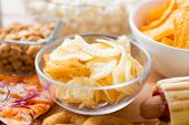fast food, junk-food, cuisine and eating concept - close up of crunchy potato crisps in glass bowl and other snacks poster