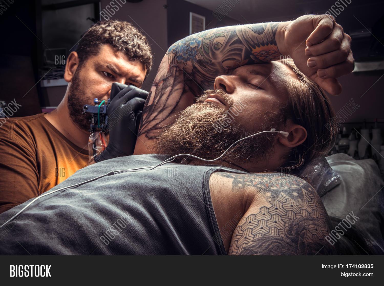 8e74f5a56 Professional tattooist makes tattoo in tattoo studio./Tattoo master working  tattooing in tattoo parlor