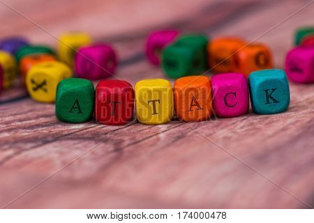 attack - word created with colored wooden cubes on desk.