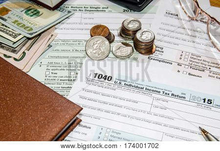 1040 tax form with dollar glasses mouse calculator notepad
