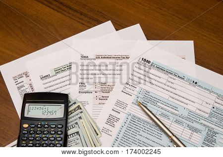 1040 Tax Return Form With Calculator On Wodden Background