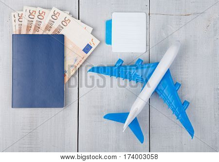 Plane, Passport, Sketchbook And Paper Money On White Wooden Table