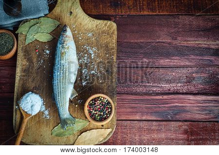 Fresh fish smelt spices for cooking on a kitchen board top view