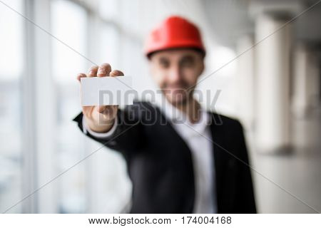 Construction worker holding blank business card, in building construction.