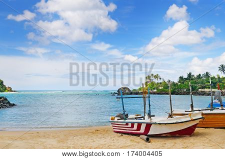 fishing boat on the sandy shore against a background the ocean and blue sky