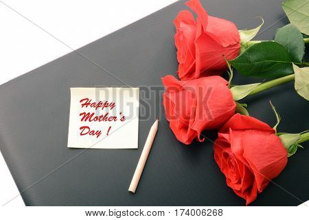 Red roses close up on a laptop isolated on white background. With note and pencil. Happy Mother Day