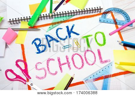 "Colorful drawing with words ""back to school"" and school accessories"