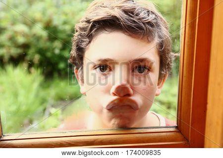 Boy Press Lips Agaist Window Glass