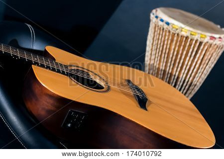 Acoustic guitar with percussion drum in studio on blue background