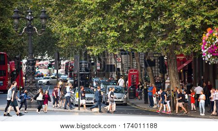 London, UK - 24 August, 2016: Northumberland avenue with lots of traffic, cars, buses and people crossing the road