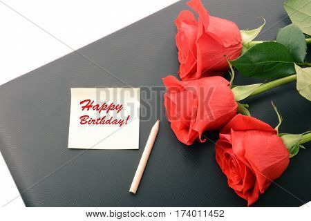 Red roses close up on a laptop isolated on white background. With note and pencil. Happy Birthday card