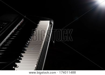 Musical piano keyboard close up with light effects in the background