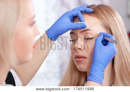 Side view of cosmetologist in gloves plucking eyebrows for beautiful woman using forceps. Woman with closed eyes enjoying of procedure of making permanent make up in beauty salon.
