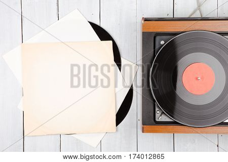 vintage music player turntable with lp on the wooden planks