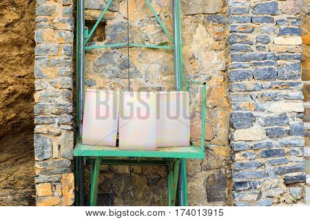 Wine box stand on miniature Elevator for lifting products from street to restaurant. Compact mechanical construction for lowering light loads. Texture of stone wall. Image contains clipping path