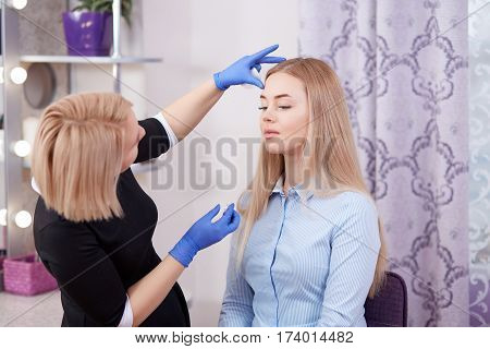 Side view of cosmetologist in black dress cleaning face her client in beauty salon looking from distanse by results. Makeup artist touching face of clent after procedure of cleaning and makeup.