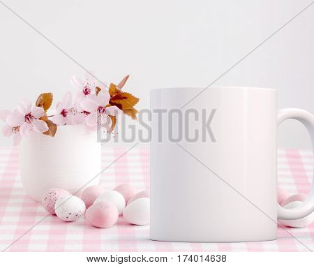 Easter Mug Mockup. Coffee mug mock-up next to blossom in a little china vase with chocolate mini eggs. Perfect for Easter mugs.