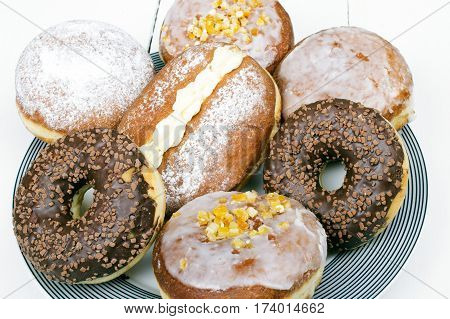 tasty donuts on a platter white wooden background
