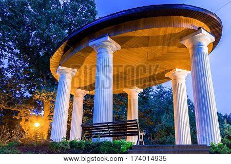 Alcove with white columns in evening park Riga