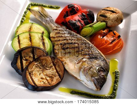Dorado fish on a white plate with vegetables grill