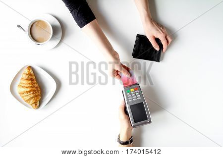 Credit card payment for business lunch in restaurant on white table background top view