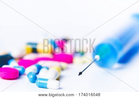 Medical equipment. Injection isolated on a white background with reflection and pills. Pharmacy background. Pills and drugs. On the top of needle is drop of water.
