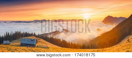 Sunrise above the high montain foggy valley with old wooden houses on a hill.