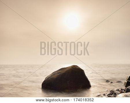 Boulders At Island Shore Stick Up From Smooth Sea. Stony Coast Defies To Waves
